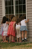 I spy. Little girls peeking inside house Stock Photos