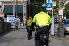 I stadens centrum ambassadör med hans karakteristiska gula skjorta och cykel i Seattle, Washington, USA arkivbilder