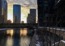 I stadens centrum Chicago som afton ställer in och reflekterar cityscape på Chicago River under vinter Arkivfoto