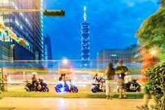 I stadens centrum gatasikt av Taipei 101 och passerad mopedkörning Royaltyfria Foton