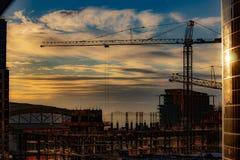 I stadens centrum solnedgång över konstruktionsplats med kranen royaltyfri bild