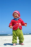 I stand already. Small girl stands on beach and it smiles royalty free stock images