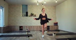 I stor rymlig en bra yogastudio se damen som hoppar på ett rep och att få en färdig kropp henne som bär en stilfull sportswear stock video