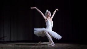 I strålar av strålkastaren på etappen av den gamla teaterkorridoren Ung ballerina i dräkten av vita svan- och pointeskor arkivfilmer