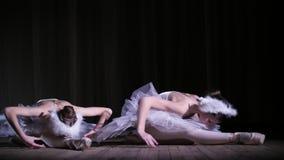 I strålar av strålkastaren på etappen av den gamla teaterkorridoren Unga ballerina i dräkter av vita svanar och pointeskor arkivfilmer
