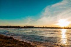 I stranden, medan solen går ner Arkivfoto