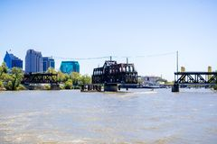 The I Street Bridge is a historic metal truss swing bridge located on I Street in Sacramento; the city's downtown skyline in the. Background, California stock photos
