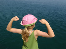 I am strong girl. A girl with pink hat and lifting arms, clenched his fist and shows his muscles, biceps, and looking into the clear blue Adriatic sea Royalty Free Stock Images