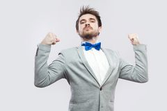 I am strong and independent. Portrait of satisfied proud handsome bearded man in casual grey suit and blue bow tie standing and. Looking at camera. indoor royalty free stock photography