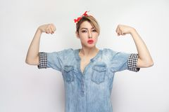 I am Strong. Portrait of independent proud satisfied beautiful young woman in blue denim shirt, makeup, red headband standing,. Looking at camera, raised arms royalty free stock photos