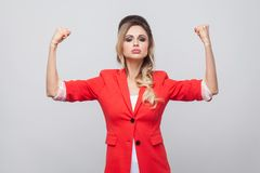 I am strong. Portrait of proud beautiful business lady with hairstyle and makeup in red fancy blazer, standing with raised arms. And looking at camera. indoor stock photography