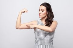 I am strong. Portrait of proud beautiful young brunette woman with makeup and striped dress standing and pointing at her biceps. Indoor studio shot, isolated royalty free stock photography