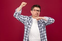 I am strong. Portrait of proud handsome middle aged business man in casual checkered shirt and eyeglasses standing and pointing at. His biceps. indoor studio royalty free stock images