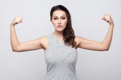 I am strong. Portrait of proud serious beautiful young brunette woman with makeup and striped dress standing, looking at camera. And showing her biceps. indoor stock photos