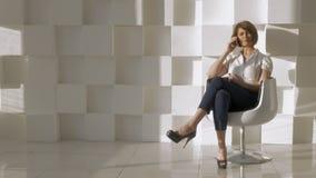 I studio ett ung flickasammanträde i en stol och samtal på en mobiltelefon stock video