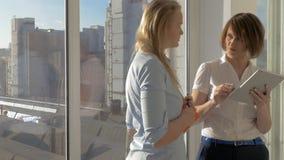 I studio två diskuterar unga kvinnor om arbete, genom att beskåda projekt på minnestavlan och därefter att göra ett avtal stock video