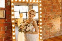 I studion står bruden i en vit klänning nära spegeln royaltyfria foton