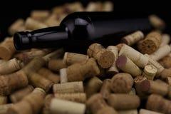 I sugheri dalle bottiglie di vino svuotano la bottiglia di vino sulla parte posteriore del nero Immagini Stock