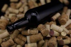 I sugheri dalle bottiglie di vino svuotano la bottiglia di vino sulla parte posteriore del nero Fotografie Stock Libere da Diritti