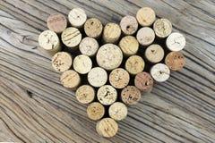 I sugheri del vino formano un'immagine di forma del cuore sul mezzo del fondo di legno del bordo Fotografie Stock Libere da Diritti