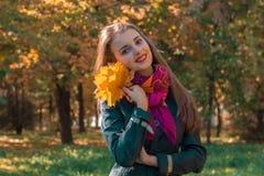 I supporti dolci della ragazza sulla testa di piegamento della via tiene le foglie ed i sorrisi Fotografie Stock Libere da Diritti