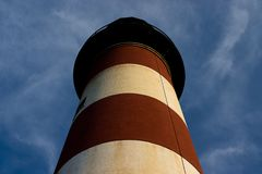 I supporti rossi e bianchi del faro alti contro un cielo blu fotografie stock libere da diritti