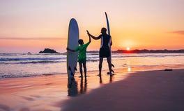 I surfisti del figlio e del padre restano sulla spiaggia del tramonto Immagini Stock