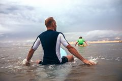 I surfisti del figlio e del padre sormontano le onde sulla linea della spuma Fotografie Stock Libere da Diritti