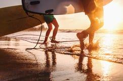 I surfisti del padre e del figlio funzionano nelle onde di oceano con i bordi lunghi Fotografia Stock Libera da Diritti