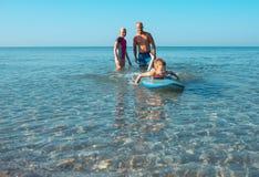 I surfisti ed il loro figlio stanno andando praticare il surfing nell'oceano in un giorno soleggiato Immagini Stock