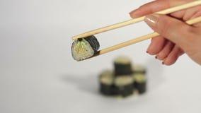 I sushi della tenuta della mano arrivano a fiumi i bastoncini, BG bianca stock footage