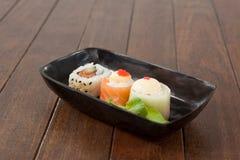 I sushi di uramaki e di Nigiri sono servito sul piatto nero della barca Fotografia Stock Libera da Diritti