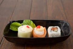 I sushi di uramaki e di Nigiri sono servito sul piatto nero della barca Immagini Stock