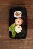 I sushi di uramaki e di Nigiri sono servito sul piatto nero della barca Fotografie Stock Libere da Diritti