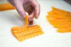 I sushi padroneggiano, tagliando i rotoli di sushi Fabbricazione dei rulli di sushi Fotografia Stock