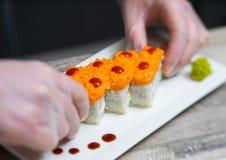 I sushi padroneggiano, tagliando i rotoli di sushi Fabbricazione dei rulli di sushi Fotografie Stock