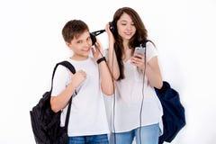 I syskongrupp lyssna till musik med hörlurar Arkivbild