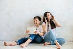 I syskongrupp lyssna till musik med hörlurar Arkivfoto