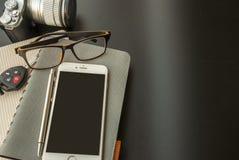 I taccuini, telefoni cellulari, vetri, macchine fotografiche, chiavi dell'automobile hanno disposto sulla tavola immagini stock libere da diritti