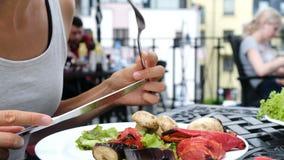 I tagli della donna un pomodoro arrostito con un coltello, la ragazza mangia una griglia delle verdure con una forcella stock footage