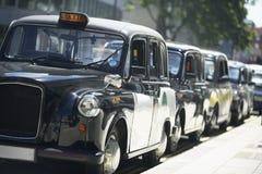 I tassì di Londra hanno allineato sul marciapiede Fotografia Stock