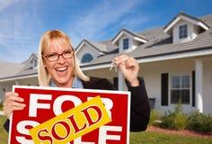I tasti femminili della holding & hanno venduto il segno del bene immobile Immagine Stock