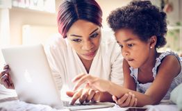 I tech you to use computer. African American mother and daughter in bed using laptop together. Space for copy. Close up stock image