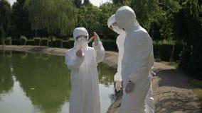 I tecnici di Hazmat team prelevando il campione infettato di acqua in un parco ed esaminandolo lago contaminato vicino - archivi video