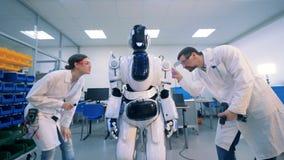 I tecnici maschii e femminili stanno eseguendo una procedura di manutenzione su un robot stock footage
