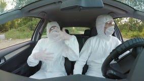I tecnici pazzi degli scienziati di rischio biologico nel hazmat è adatto al dancing ed all'azionamento al lavoro in un automobil stock footage
