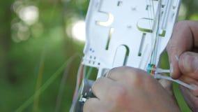 I tecnici stanno installando la fibra ottica con le fascette ferma-cavo stock footage