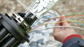 I tecnici stanno installando la fibra ottica con le fascette ferma-cavo immagini stock libere da diritti
