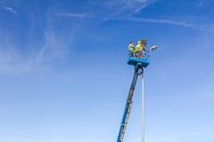 I tecnici stanno lavorando in un secchio su su su una torre del riflettore Immagini Stock