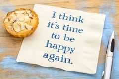 I think it is time to be happy again. I think it`s time to be happy again - handwriting on a napkin with a French almond cookie Stock Photos